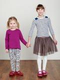 Deux filles tiennent des mains, souriant Image libre de droits