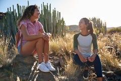 Deux filles trimardantes prenant un repos Images stock