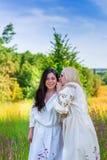 Deux filles ukrainiennes dans des costumes nationaux au pré de fleur Photos stock