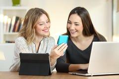 Deux filles vérifiant l'information dans des dispositifs multiples photographie stock