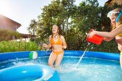 Deux filles versant l'eau d'un seau rouge dans la piscine Photo stock
