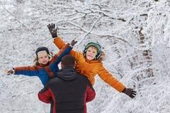 Deux fils et son père en parc d'hiver fixation amusement, joie, bonheur, amitié Image stock