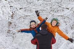 Deux fils et son père en parc d'hiver fixation amusement, joie, bonheur, amitié Photographie stock