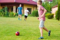 Deux fils heureux jouant le football avec leur père dans le jardin près Photos stock