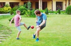 Deux fils heureux jouant le football avec leur père dans le jardin près Images stock