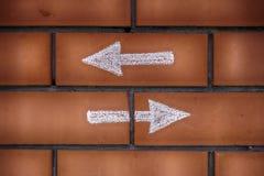 Deux flèches se dirigeant en avant et vers l'arrière dessiné sur des briques Photos stock