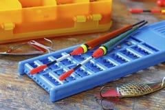 Deux flotteurs de pêche avec les appâts et accessoires sur une table en bois Image stock