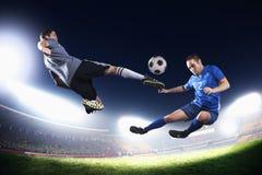 Deux footballeurs dans le plein vol donnant un coup de pied le ballon de football, stade s'allume la nuit à l'arrière-plan Images stock