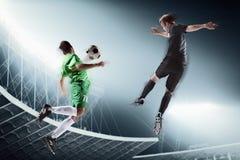 Deux footballeurs donnant un coup de pied un ballon de football Photos libres de droits
