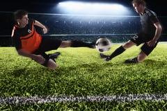 Deux footballeurs donnant un coup de pied un ballon de football Images libres de droits