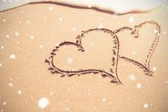 Deux formes de coeur dessinées sur le sable Photographie stock libre de droits