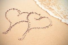 Deux formes de coeur s'inscrivent sur le sable Photographie stock libre de droits