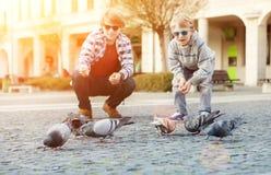 Deux frères alimentent des colombes sur la vieille place de ville Image stock
