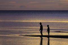 Deux frères apprécient sur la plage avec la mer colorée dans le lever de soleil Images stock