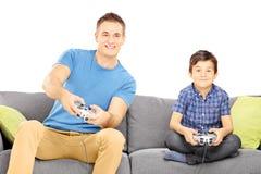 Deux frères assis sur un sofa jouant le jeu vidéo Photographie stock libre de droits