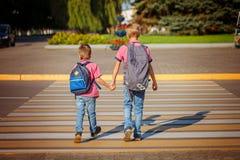 Deux frères avec la marche de sac à dos, tenant dessus le jour chaud sur Photographie stock libre de droits