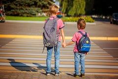 Deux frères avec la marche de sac à dos, tenant dessus le jour chaud sur Photographie stock