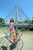 Deux frères heureux jouant sur le terrain de jeu avec les cordes et le scaf Photos stock