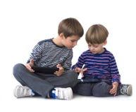 Deux frères jouant des jeux vidéo sur des tablettes Image libre de droits