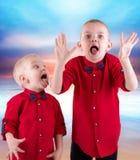 Deux frères jouant et ayant l'amusement, Hamming passant le temps ensemble Ils portent le même habillement à la mode, chemises images libres de droits