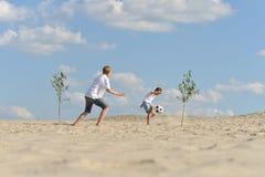 Deux frères jouant le football sur la plage dans le jour d'été photo stock