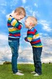 Deux frères jouent, ont l'amusement, font des amis Enfants habillés dans les mêmes vêtements Image libre de droits