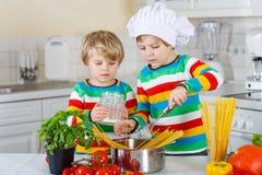 Deux frères mignons faisant cuire le repas italien avec le spahetti Photo stock
