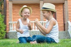 Deux frères s'asseyant sur l'herbe et manger l'épi de maïs dans le jardin Jeux fun, rire photo stock