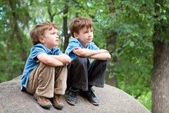 Deux frères s'asseyant sur la roche Photos libres de droits