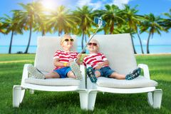 Deux frères se trouvant sur les canapés du soleil et prendre le selfie au téléphone portable Vacances d'été chaudes images libres de droits