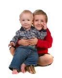 Deux frères souriant et s'asseyant ensemble sur le blanc photo libre de droits