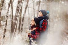 Deux frères sur le walr dans des meilleurs amis de forêt d'hiver jouant ensemble Photos stock