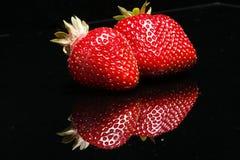 Deux fraises sur le noir Photos libres de droits
