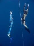 Deux freedivers se lèvent de la profondeur du trou bleu photo libre de droits