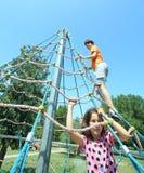 Deux frères jouant sur le terrain de jeu sur un carrousel avec des cordes Images libres de droits
