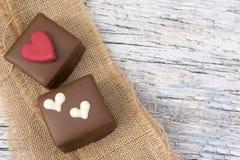 Deux gâteaux de chocolat décorés des coeurs sur la toile de jute Images libres de droits
