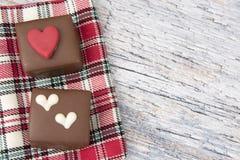 Deux gâteaux de chocolat décorés des coeurs sur un tissu rouge Photo libre de droits