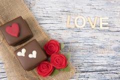 Deux gâteaux de chocolat décorés des roses sur la toile de jute Photos stock