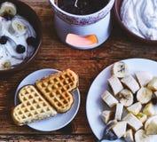Deux gâteaux de gaufrette sous forme de coeur se trouvent d'un petit plat sur une table en bois servie Photo stock