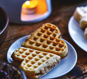 Deux gâteaux de gaufrette sous forme de coeur se trouvent d'un petit plat sur une table en bois servie Photographie stock libre de droits