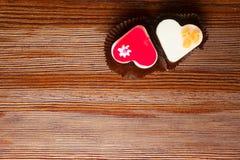 deux gâteaux frais, rouge et blanc, coeur forme sur le fond en bois Gâteaux délicieux d'amour Images stock