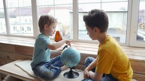 Deux garçons étudiant la géographie de la terre avec un globe clips vidéos