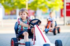 Deux garçons actifs de petit enfant conduisant la voiture de course de pédale en été Image stock