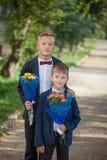 Deux garçons adorables avec un beau bouquet des fleurs sur le fond de nature photographie stock libre de droits
