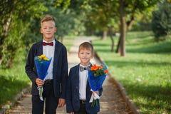 Deux garçons adorables avec un beau bouquet des fleurs sur le fond de nature photo stock
