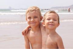 Deux garçons adorables mignons de petits frères s'asseyant sur la mer d'océan de plage Photographie stock