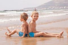 Deux garçons adorables mignons de petits frères s'asseyant sur la mer d'océan de plage Photos libres de droits