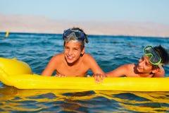Deux garçons apprécient leur temps sur la plage photos libres de droits