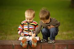 Deux garçons apprennent à s'afficher et écrire Photos libres de droits