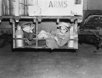 Deux garçons avec des boîtes métalliques de lait dans une baie de cargaison d'un camion (toutes les personnes représentées ne son Photo libre de droits